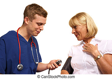 Doctor in scrubs taking the blood pressure of a mature female patient