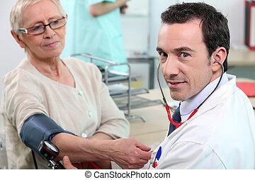 Doctor taking tension to senior woman