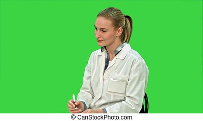 Doctor talking to a patient, giving consultation sitting on a Green Screen, Chroma Key.