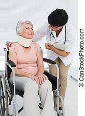 Doctor talking to a senior patient in wheelchair with cervical collar at the hospital