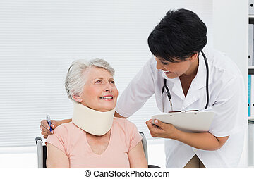 Doctor talking to a senior patient with cervical collar