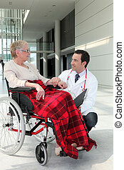 Doctor talking to an elderly woman in a wheelchair