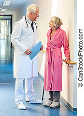 Doctor talking to an elderly woman in the corridor.