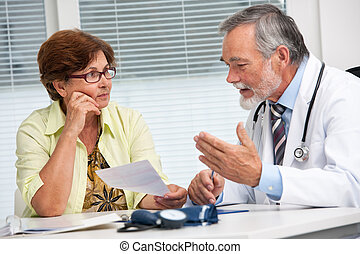 Doctor talking to his female senior patient at the office