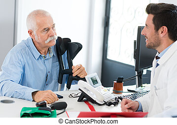 doctor talking to old man with crutches