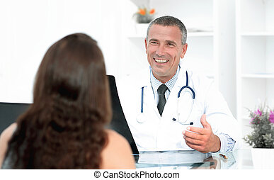 Doctor talking to patient sitting at the table.the concept...