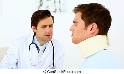 Doctor talking to patient with a neck injury in his office...