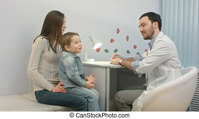 Doctor talking to young child and mother