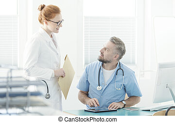 Doctor talking with assistant