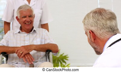 Doctor talking with elderly patient in a wheelchair being ...