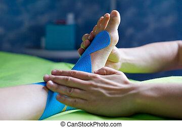 Doctor taping woman injury leg.