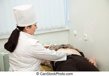 Doctor touching  stomach of patient