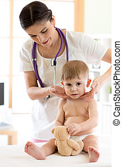 Doctor touching the throat of child patient in the office -...