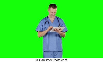 Doctor uses a tablet and shows thumb. Green screen
