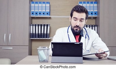 Doctor using a tablet pc to talk through video conference with his patient