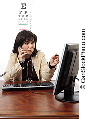 A busy female medical doctor sits at office desk using the computer whilst taking a telephone call.