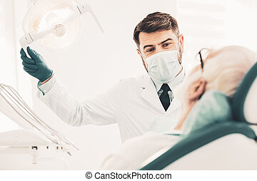 Doctor using dental lamp during appointment