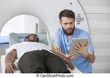 Doctor Using Digital Tablet By Patient Lying On CT Scanner