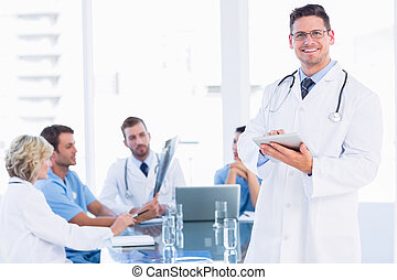Doctor using digital tablet with colleagues in meeting
