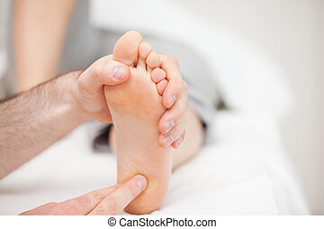 Doctor using his fingertips to touch the ball of a foot in a...