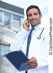 Doctor using his mobile phone outside a hospital building