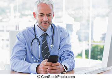 Doctor using his smartphone in the office at desk