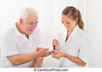 Doctor Using Lancelet On Patient's Finger