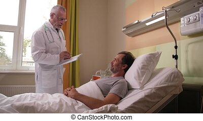 Grey-haired practitioner in doctor's white robe communicating with sick man recovering after surgery in hospital ward. Aging physician standing near patient's bed talking about postoperative treatment