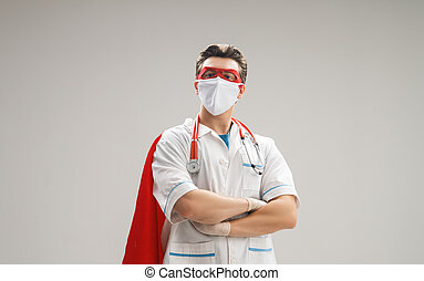 Doctor wearing facemask and superhero cape during ...