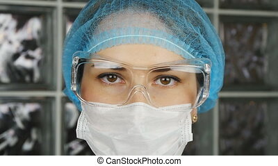 Doctor wearing glasses, surgical mask and gloves, medical...
