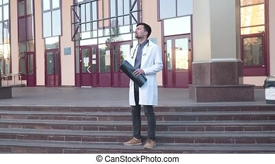 Doctor wearing lab coat stethoscope analyzing X-ray image outdoors stand near hospital main entrance. Young healthcare professional, internet radiologist exam mri x-ray lungs during COVID 19 epidemic.