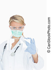Doctor wearing surgical gear looking at glass pane