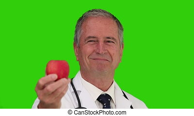 Doctor with a stethoscope holding an apple