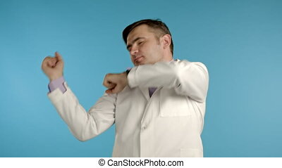 Doctor with beard funny dancing, success and luck at work. Young handsome doc man in professional medical white coat is isolated on blue studio background. High quality 4k footage