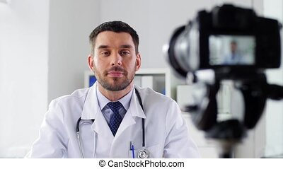 healthcare, medicine and blogging concept - male doctor with camera recording video blog at hospital