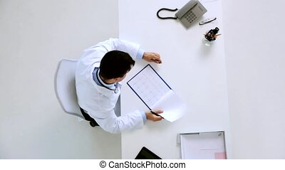 doctor with cardiogram on clipboard at clinic