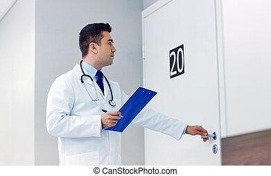 doctor with clipboard opening hospital ward door - clinic,...