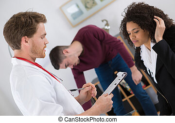 Doctor with clipboard talking to young woman