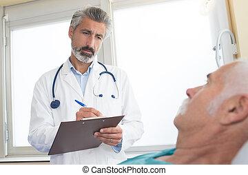 doctor with clipboard visiting senior man at hospital ward