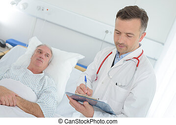 doctor with clipboard visiting senior patient at hospital ward