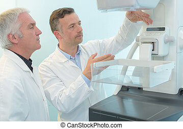 doctor with colleague next to ct machine with scan results