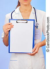 Doctor with copyspaced clipboard waist-high portrait on blue
