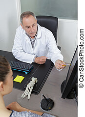 doctor with female patient pointing on computer