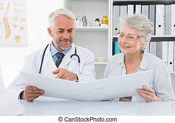Doctor with female patient reading reports