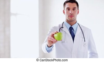 doctor with green apple in hands - professional doctor with...