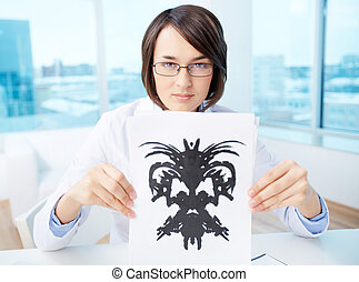Doctor with inkblot - Serious psychologist showing paper...