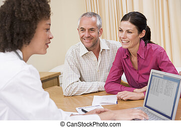 Doctor with laptop and couple in doctor\'s office smiling