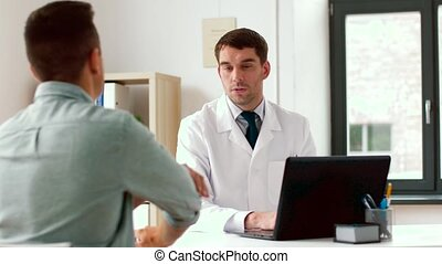 doctor with laptop and male patient at hospital - medicine,...