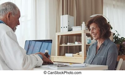 Doctor with laptop talking to a senior woman in office.