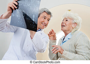 Doctor With Patient Looking At X-ray - Happy mature male...